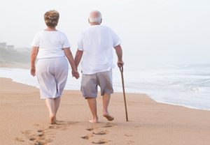 Senior Couple Walking Hand in Hand Down the Beach