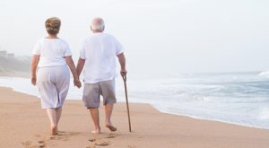 Senior Couple Walking Down the Beach Hand in Hand